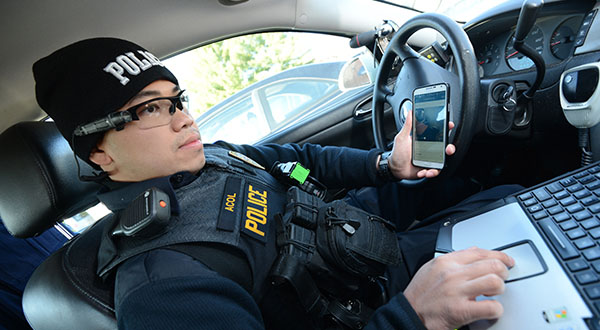 Interoperability - MD Officer seen here at his squad car with his head mounted-point of view video recording system, that he can connect with an app on his cell phone to view footage recorded.